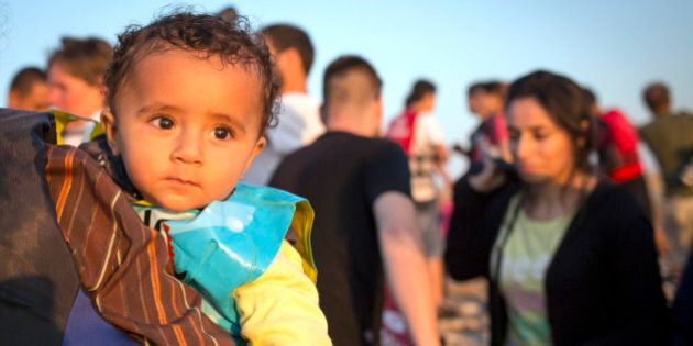 A migrant baby looks towards the see as migrants arrive on a dinghy at the southeastern island of Kos,...
