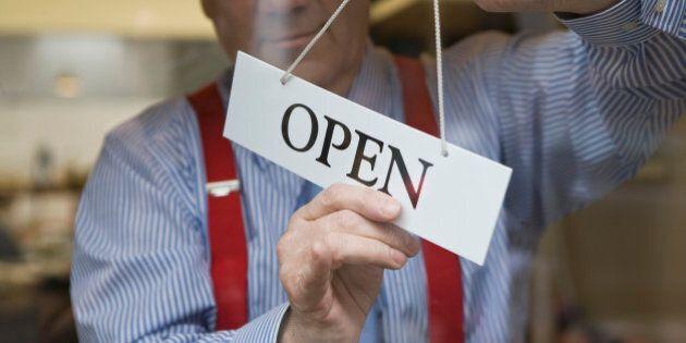 Man hanging open sign on door