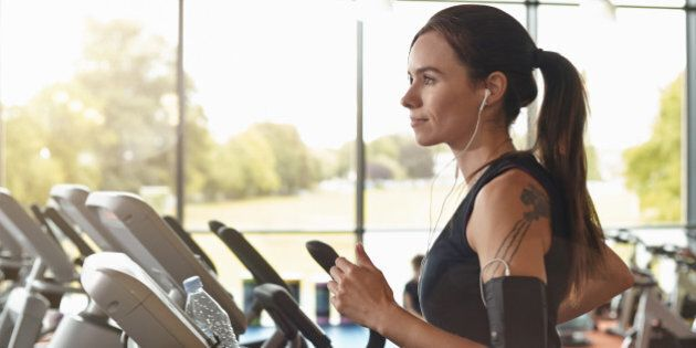 Woman in a gym on a running machine, she has headphones in a smartphone in an arm