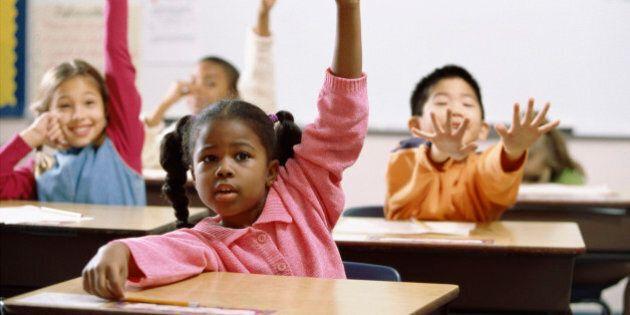 School children raising their hands in class