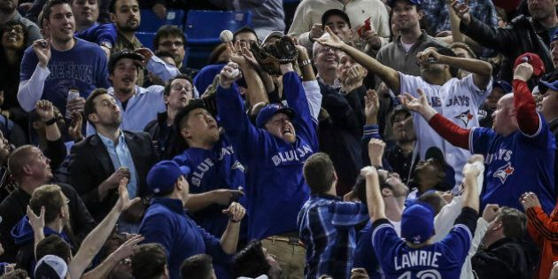 TORONTO, ON - APRIL 19  - Blue jays fans try for a foul ball along the first base line during the Toronto Blue Jays take on the New York Yankees at The Rogers Centre April 19, 2013.        (David Cooper/Toronto Star via Getty Images)