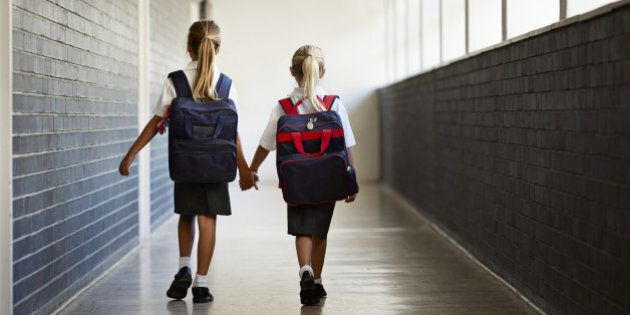 Schoolgirls walking hand in hand at school