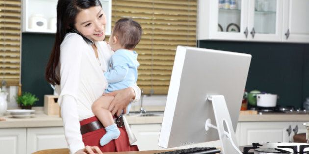 Businesswoman using computer while carrying baby