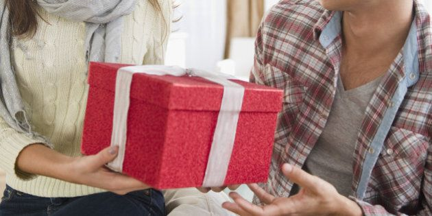 Woman handing husband Christmas