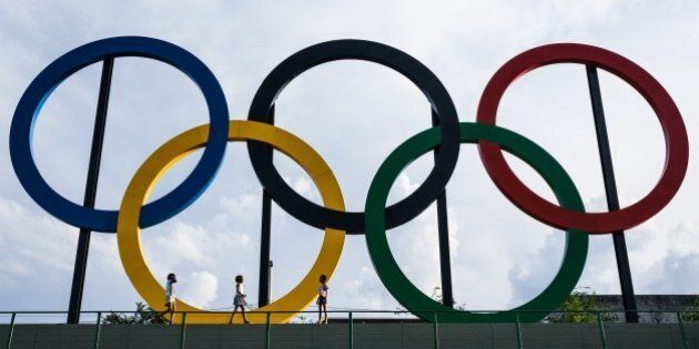 Youngsters walk past the Olympic rings at Madureira Park, the third largest park in Rio de Janeiro, Brazil,...