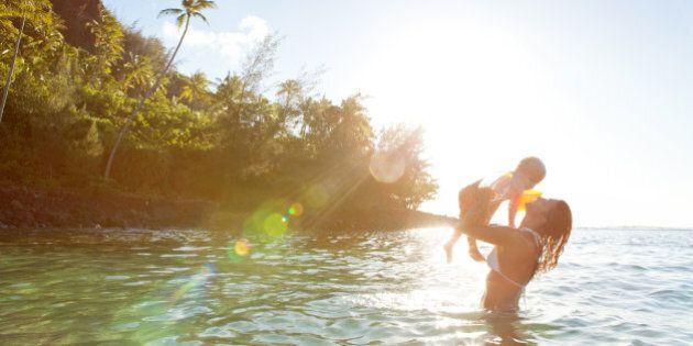 Mother and son having fun at tropical Kee Beach in Kauai, Hawaii, USA.