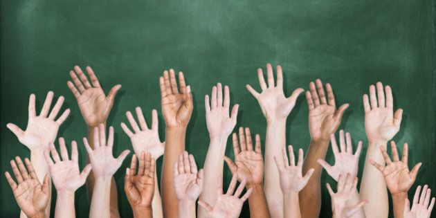 A multi-ethnic group of students' hands raised in front of a classroom blackboard. There are 18 hands...