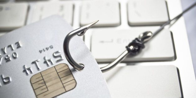 phishing - fish hook with a credit card on white computer