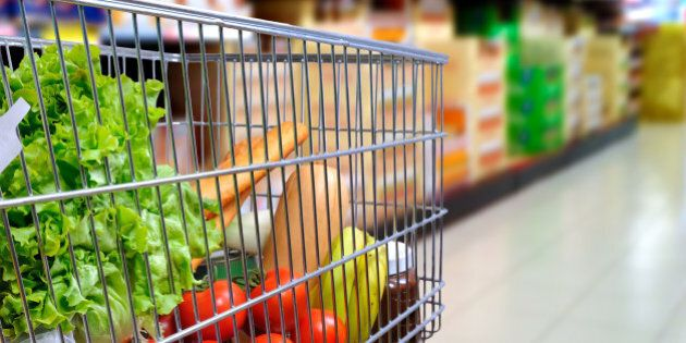 Shopping cart full of food in the supermarket aisle. Side tilt view. Horizontal