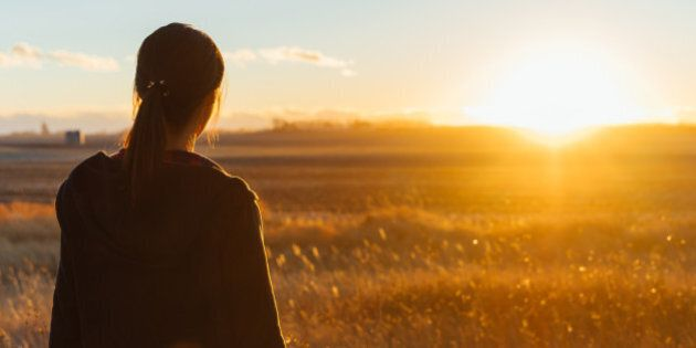 A Japanese woman is standing in a grassy field seeing the sunset in the