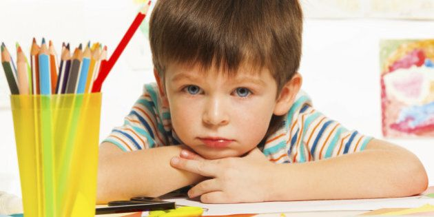 Close portrait of boy with pencils and color paper