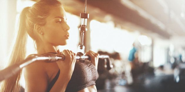 Closeup side view of an attractive brunette working out at a gym. She's using lat pull down machine with...