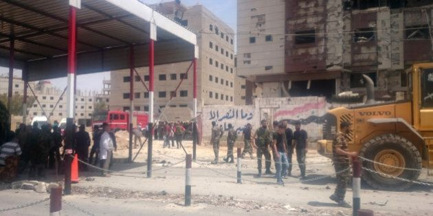 Syrian security forces gather at the site of a car bomb near the revered Shiite shrine of Sayyida Zeinab,...