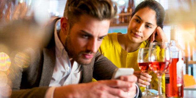 A couple are out having drinks and the woman looks irritated that her partner is on his mobile phone...