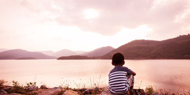 little boy sitting alone at dam in the