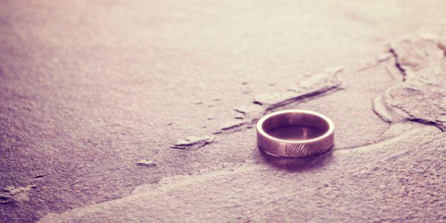 Vintage toned single weeding ring on stone background, conceptual