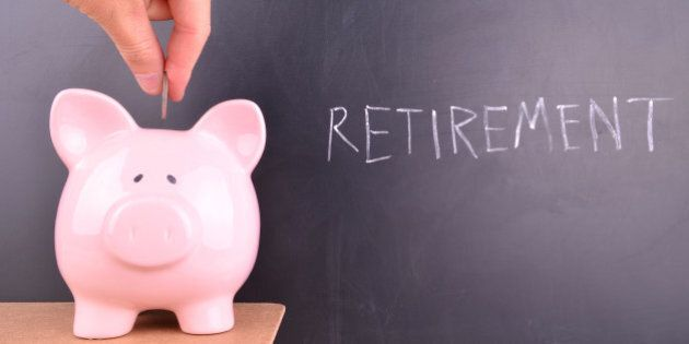 Depositing coins and money into a pink piggybank with retirement written in white chalk on a blackboard