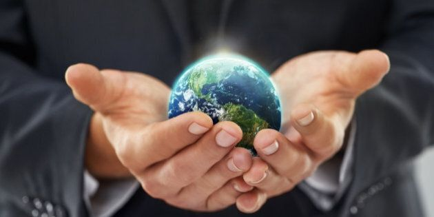 Cropped image of a businessman holding a globe in his cupped