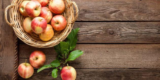 fresh apples in wicker basket on wooden