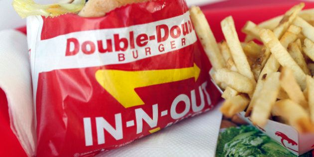 A Double-Double burger and french fries are arranged for a photograph at an In-N-Out Burger restaurant...