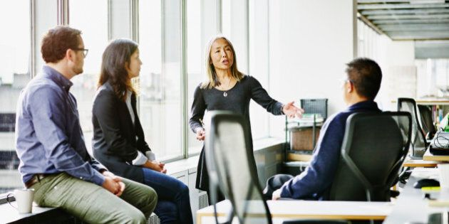 Mature businesswoman leading discussion during team meeting with coworkers in