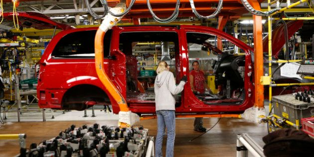 Fiat Chrysler assembly workers work on a partially assembled minivan at the Windsor Assembly Plant in Windsor, Ontario, February 9, 2015. The plant prepares to shut down for 14 weeks starting February 16 in preparation for Fiat Chrysler's next generation minivan. REUTERS/Rebecca Cook (CANADA - Tags: TRANSPORT BUSINESS)