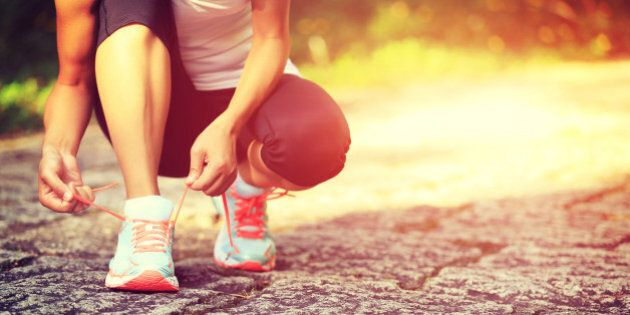young fitness woman runner tying shoelaces on