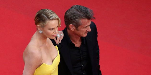 Actors Sean Penn, right, and Charlize Theron pose for photographers as they arrive for the screening...