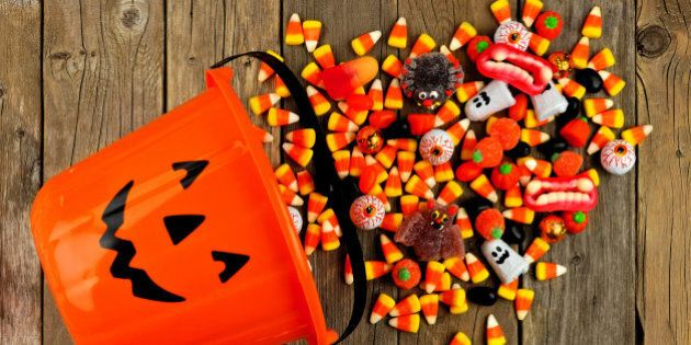 Halloween Jack o Lantern pail with spilling candy, above view on a rustic wood
