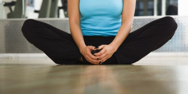 Young woman in a gym looking forward preforming a groin stretching exercise. Horizontal shot.