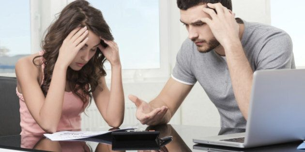Couple, Man angry and upset after looking at credit card statement.