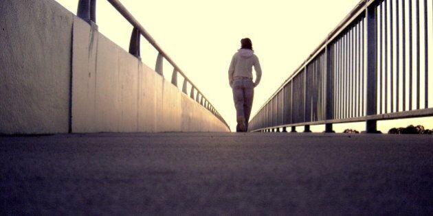 A lonely girl walking along bridge.