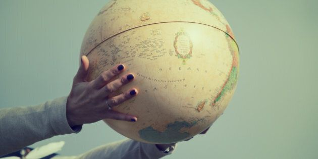 Hands holding a globe. Vintage tone effect.