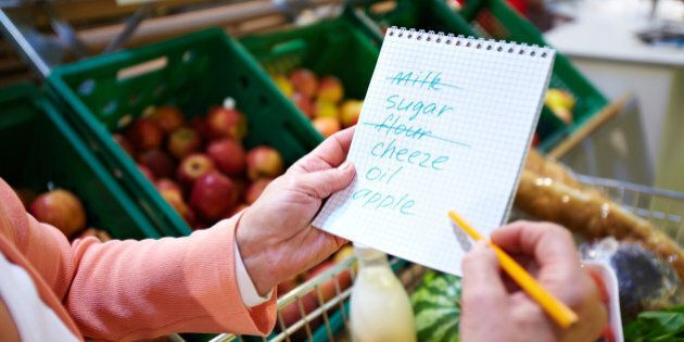 Image of senior woman hands holding product list with goods in cart near by