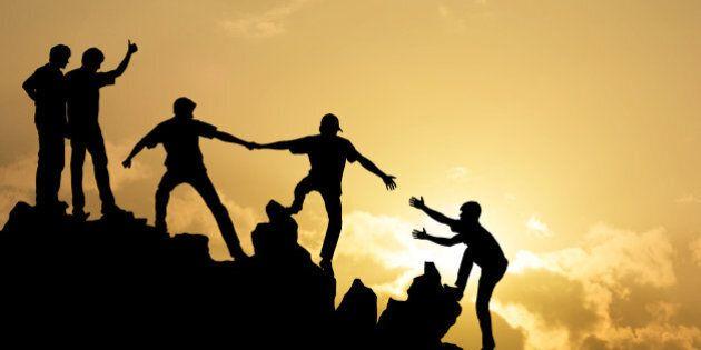 Group of people on peak mountain climbing helping team work , success