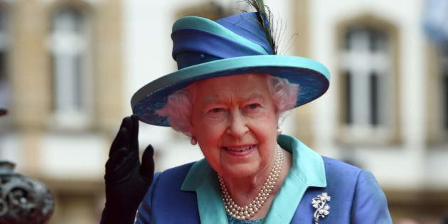 Britain's Queen Elizabeth II waves to the crowd on her way to the city hall in Frankfurt, central Germany,...