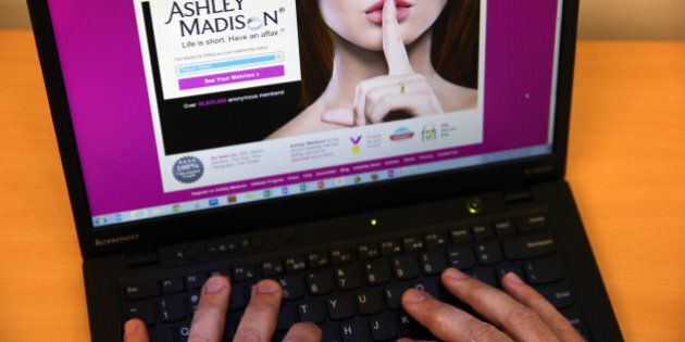 LONDON, ENGLAND - AUGUST 19: In this photo illustration, a man visits the Ashley Madison website on August...