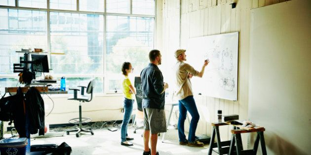 Engineer sketching project plans on whiteboard with coworkers in workshop