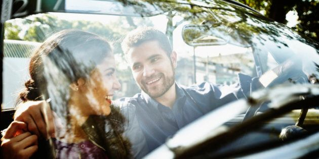 Smiling couple embracing in front seat of
