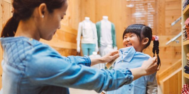 Pretty young mom fitting a shirt on the cheerful little girl at the kid's wear department in a fashion boutique