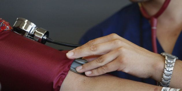 A healthcare aide checks the blood pressure of a patient during the Care Harbor Public Health Clinic...