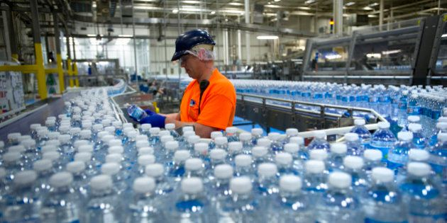 A worker inspects bottles of water at the Nestle Waters Canada plant near Guelph, Ontario, Canada, on...