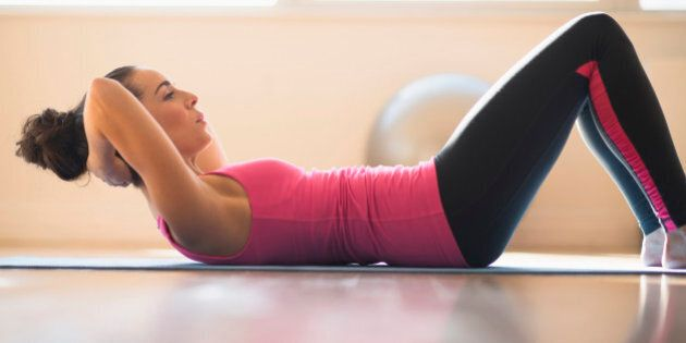 Close up of Hispanic woman doing sit-ups in gym
