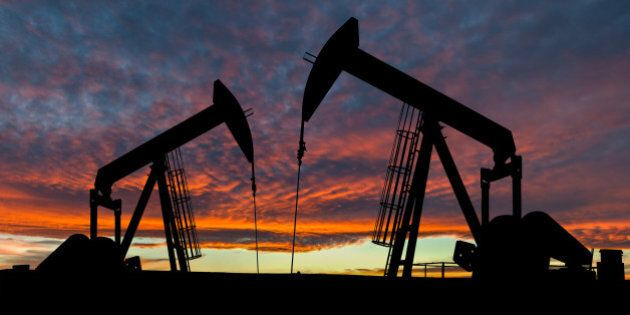 Dramatic sky over two pumpjacks in rural Alberta, Canada. These jacks can extract between 5 to 40 litres...