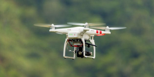 Drone with camera flying through nature.