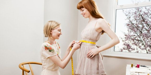 woman measuring waist of other woman's dress.