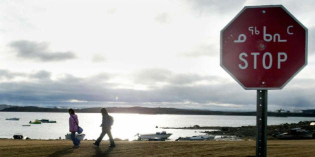Iqaluit, CANADA:  (FILES): This 02 October 2002 file photo shows two Inuit children returning from school in Iqaluit, northern Canada, past a stop sign written in both English and Inuit. Researchers from some 60 countries will try to better understand the Earth's poles in 2007 and the effect of climate change as part of the first 'International Polar Year' since the 1950s.  The scientific effort, unlike previous undertakings, will be marked by the specter of global warming and transformed by collaboration with Inuits living in the Arctic.  AFP PHOTO/FILES/Andre FORGET  (Photo credit should read ANDRE FORGET/AFP/Getty Images)