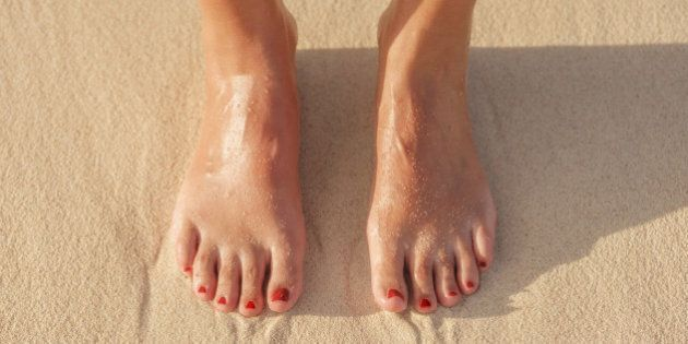 Close up of Hispanic woman's feet in sand on
