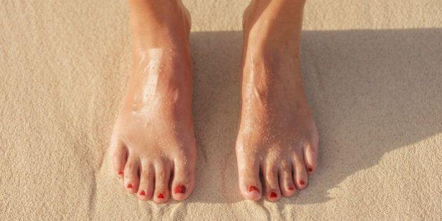 Close up of Hispanic woman's feet in sand on beach