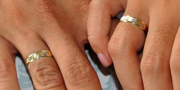 A couple holds hands showing their wedding rings during a mass wedding of 250 couple in Manila on October...